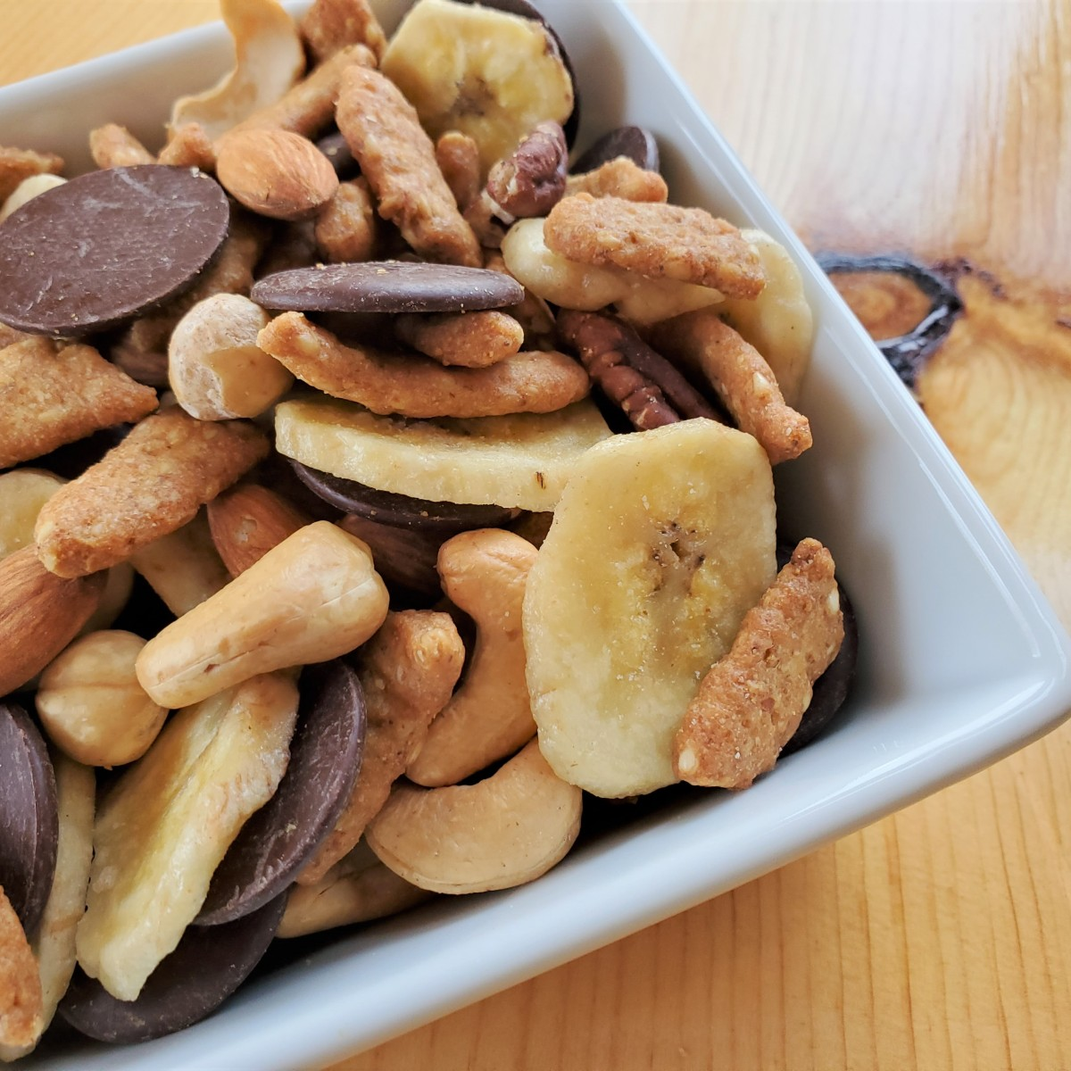White square bowl on a wooden table filled with mixed ingredients. Brown sesame sticks, round, tellow banana chips, mixed variations of brown and beige nuts, and round smooth dark chocolate wafers fill the white dish.